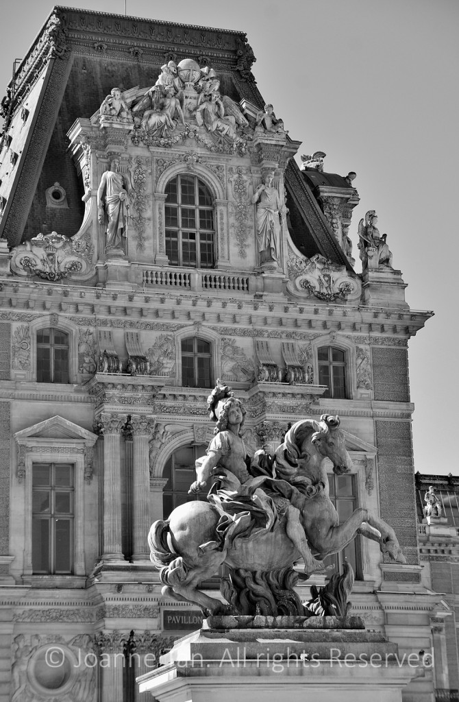 A section of the exterior of the Louvre Palace is ornately adorned with statues, beneath which another free-standing sculpture of a man on a horse. Paris, France.