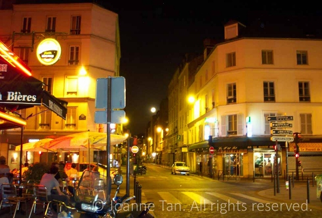 Street lights and a full Parisian/Parisien Moon aglowing the buildings with yellow, orange colors, a Restaurant diners sitting outside on the street corner, on a hot summer night. Paris, France.