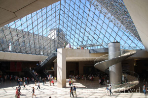An interior view towards the sky light ceiling & structure, with the old Louvre Palace & water shooting up from the fountain outside of the glass & metal pyramind. A modern structure with spiral staircase, free standing cube column, and sunlight on people walking inside.