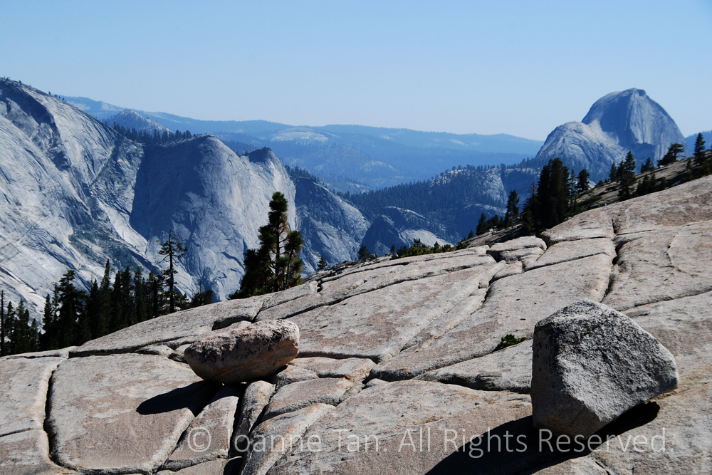 Two rocks in balance on a huge slap of granite with natural grooves and lines, in the blue background is the top of Half Dome and the granite domes and the Sierra Mountains in Yosemite, CA. An eagle flying against the granite mountain lined by pine forest.